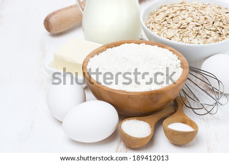milk, cereal and ingredients for baking on wooden table, horizontal, close-up - stock photo