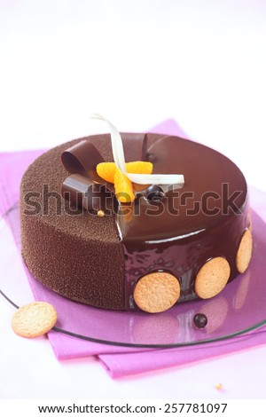 Milk Chocolate, Black Currant and Spiced Tangerine Entremet Cake coated with chocolate velvet spray and mirror glaze, decorated with chocolate elements and tangerine slices, on a purple napkin. - stock photo