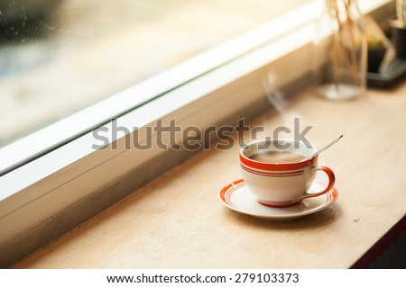 Milk coffee in coffee cup on wood bar with morning scene - stock photo