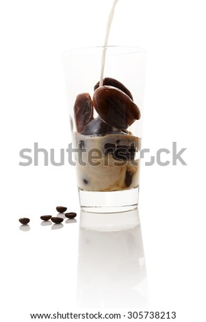 Milk coffee. Pouring milk on frozen coffee in coffee bean form in glass on white background. Culinary coffee drinking.  - stock photo