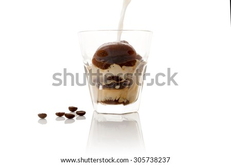 Milk coffee. Pouring milk on frozen ice coffee beans in glass on white background. Culinary coffee drinking.  - stock photo