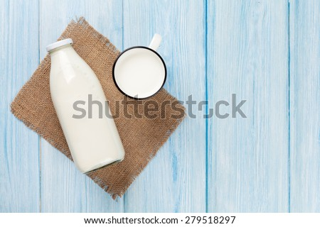 Milk cup and bottle on blue wooden table. Top view with copy space  - stock photo