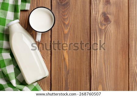 Milk cup and bottle on wooden table. Top view with copy space - stock photo