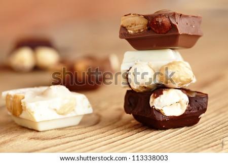 Milk, dark and white chocolate with nuts - stock photo