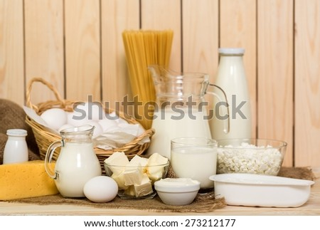 Milk. Fresh farm dairy products on a white wooden background. Tasty cheese, butter, eggs, milk and yogurt close-up. - stock photo