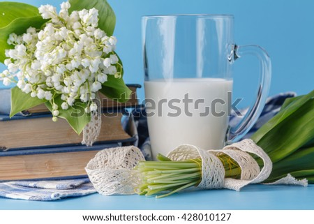 Milk glass on the blue with flowers - stock photo