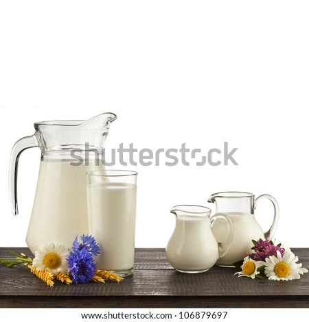 Milk in a glass on the wooden table isolated on white background - stock photo