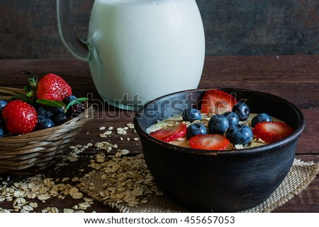 Milk in a jug and oatmeal porridge in a pottery bowl with fresh ripe berries in a wicker bowl standing on canvas on wooden table. healthy breakfast - stock photo