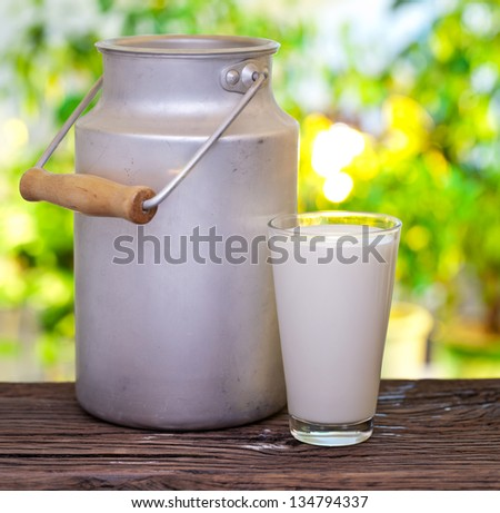 Milk in aluminum can and glass on the old wooden table on outdoor setting. - stock photo