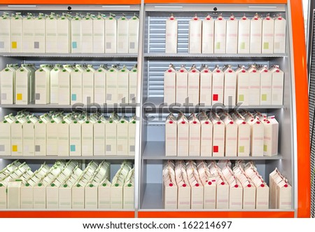 Milk in carton packaging at store shelf - stock photo