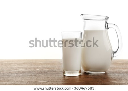 Milk in glass and in jar on table isolated on white background - stock photo