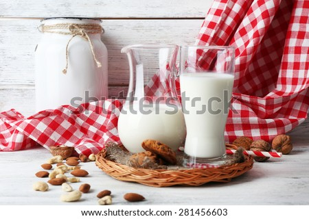 Milk in glassware with walnuts and cookies on wooden table with napkin, closeup - stock photo