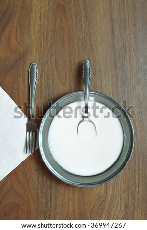 Milk in metal plate on table. - stock photo