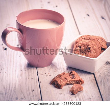milk in pink cup with cookies on wood table - stock photo