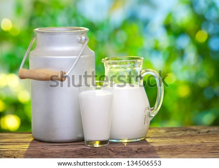 Milk in various dishes on the old wooden table in an outdoor setting. - stock photo