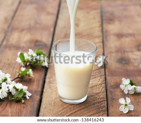 milk is flowing down to glass on wooden table - stock photo