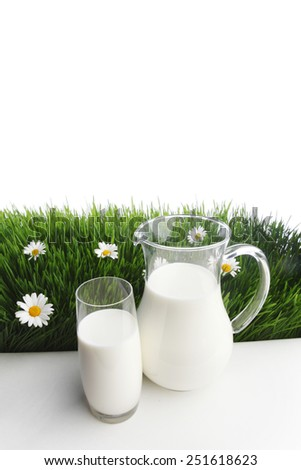 Milk jug and glass on fresh green grass with chamomiles isolated on white - stock photo