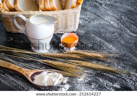 milk jug and products for baking on a black  textured table - stock photo
