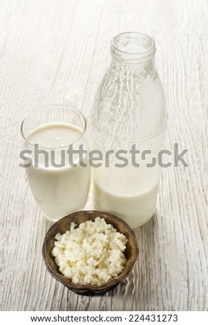 Milk kefir and grains in glass on wooden table - stock photo