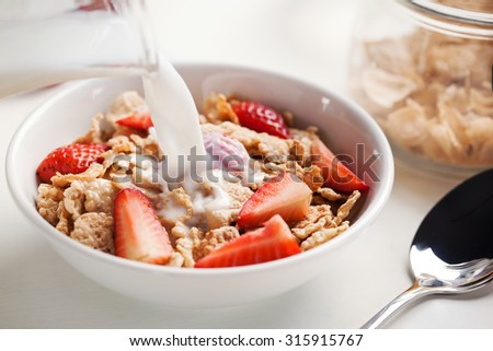 milk pourin g in cereal with strawberry for breakfast - stock photo
