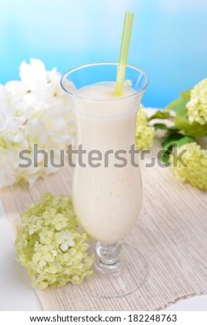 Milk shake on table on light blue background - stock photo