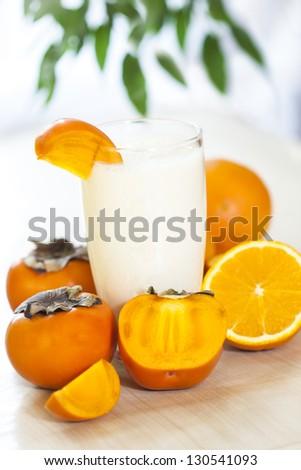 Milk shake with fruit -  orange and kaki. - stock photo