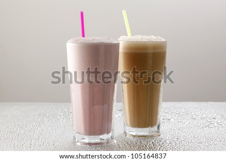 Milk shakes (strawberry and Chocolate) on water drops background - stock photo