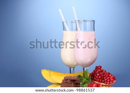 Milk shakes with fruits and chocolate on blue background - stock photo