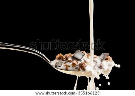 Milk splashing against silver spoon filled with cereals and chocolate over black background - stock photo