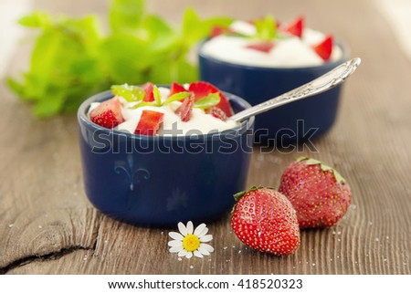 Milk strawberries dessert. Whipped cream with strawberries. Serving tasty treats from dairy cream and red strawberries standing on the wooden table. Berries and cream. - stock photo