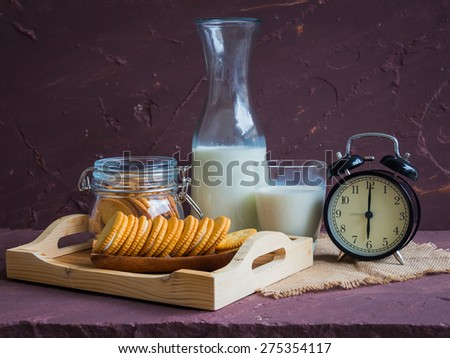 Milk with sandwich cracker and vintage black clock on brown stone table over stone grunge background.  - stock photo