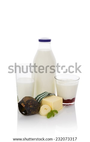 Milk, yogurt and butter. Traditional dairy products high in calcium with traditional austrian cow bell isolated on white background.  - stock photo