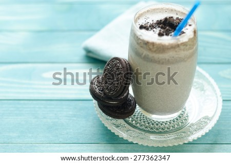 Milkshake (chocolate smoothie)  in a glass on colorful turquoise blue painted wooden boards. - stock photo