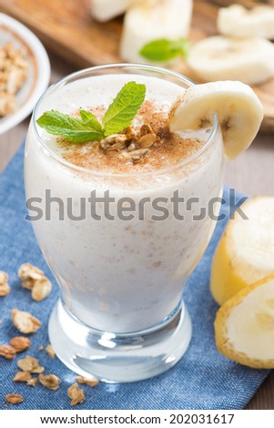 milkshake with banana, granola and cinnamon, close-up, vertical - stock photo