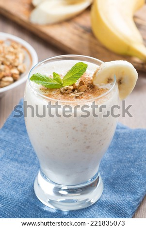 milkshake with banana, granola and cinnamon in a glass, vertical - stock photo