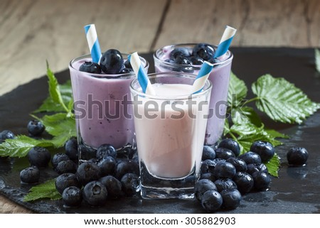 Milkshake with wild blueberries and blackberries with striped straws on a dark background, selective focus - stock photo