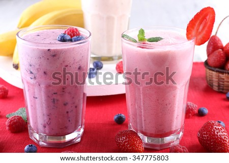 Milkshakes with berries at red textile on light background - stock photo