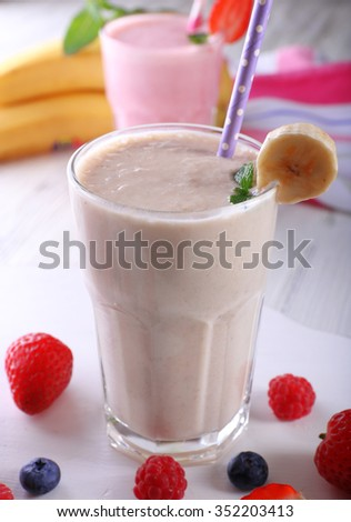 Milkshakes with berries on light wooden background, close-up - stock photo