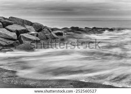 Milky waves splashing over rocks in black and white - stock photo