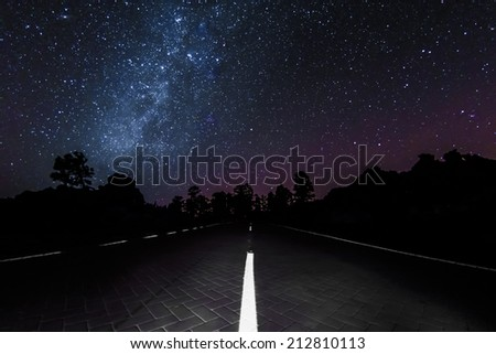 Milky Way above a road through Teide National Park at Tenerife - stock photo