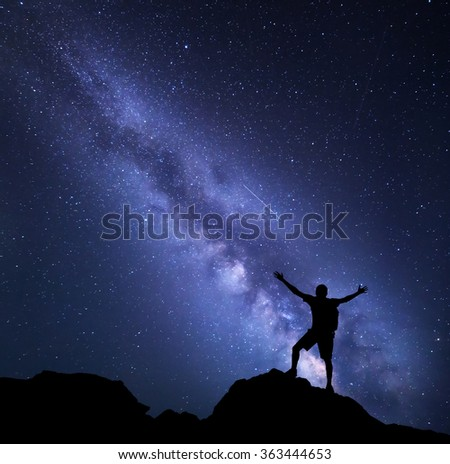 Milky Way. Night sky with stars and silhouette of a happy man with backpack and raised up arms. Space background - stock photo