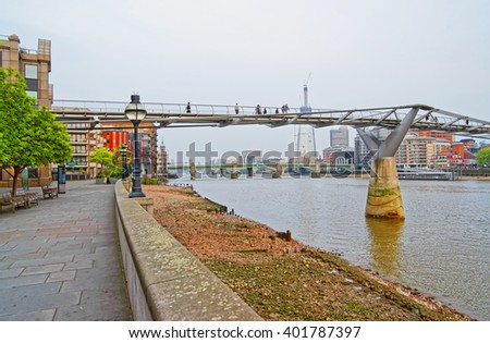 Millennium Bridge in London in England. It is also called the London Millennium footbridge. The street view with tourists. - stock photo
