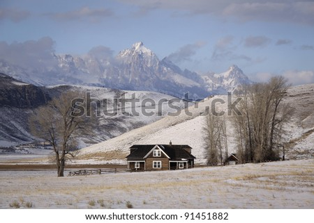 Miller Cabin in Jackson Hole Wyoming during winter with Teton Mountains in the background and snow on the ground - stock photo