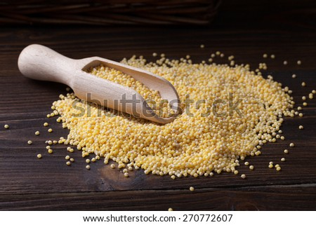 millet in a spoon on a wooden table - stock photo