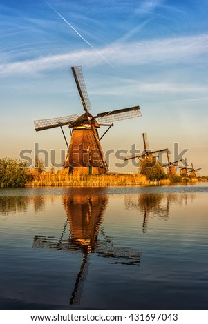 Mills in Netherland, Kinderdijk - scenic sunset landscape with windmills, blue sky and reflection in the water at soft light. Vertical image, nature background - stock photo