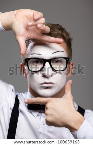 Mime face and hands in a black bow tie and glasses a theatrical make-up isolated on gray background - stock photo