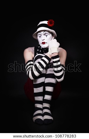 Mime in a white hat sitting on the floor - stock photo