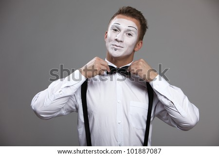 Mime man corrects both hands a bow tie - stock photo