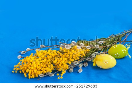 Mimosa, twigs of willow and easter eggs on a blue background - stock photo