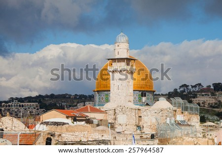 Minaret against the Dome of the Rock in Jerusalem and dramatic cloudy sky - stock photo